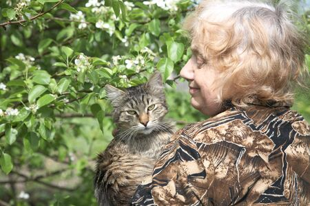 The old woman holds on hands cat against a blossoming tree