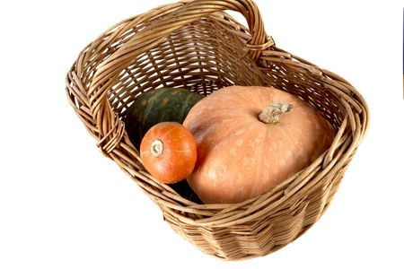 Yellow and  striped pumpkin in  wattled basket on a white background photo