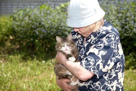 The old woman holds cat on hands photo