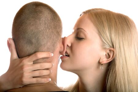 The girl bites an ear of the young man on a white background