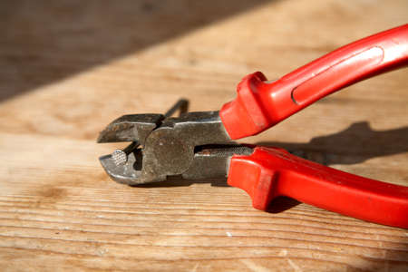 clamped: Nippers with the clamped nail on a wooden table
