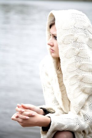 The thoughtful girl in  knitted dress on a background of water Stock Photo