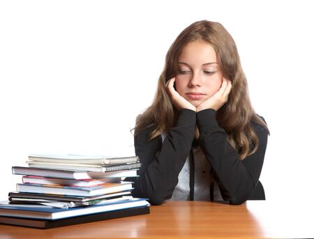 The girl-teenager looks at  pile of books on a white background
