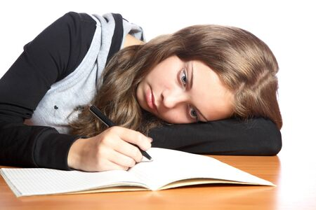 The girl-teenager looks in  writing-book on a white background photo