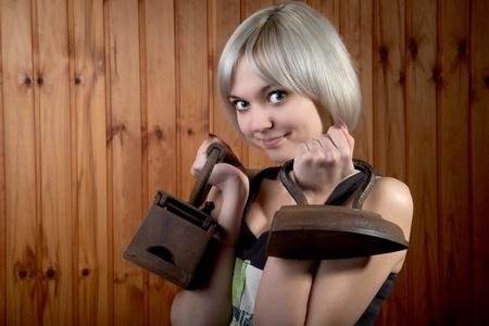 pesantezza: La ragazza con vecchi ferri da stiro e un aspetto arco  Archivio Fotografico