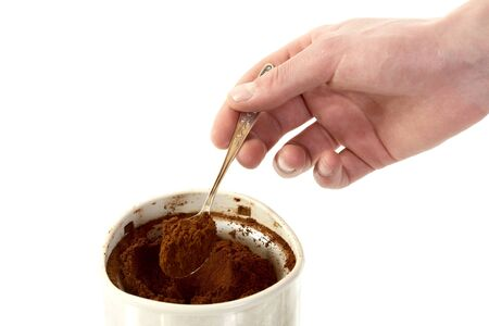 The mans hand with spoon takes coffee from  coffee grinder on a white background photo
