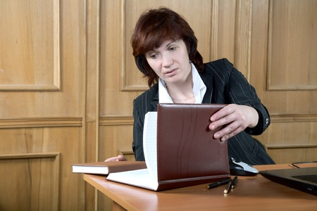 The woman of average years opens an organizer at office Stock Photo - 9206642