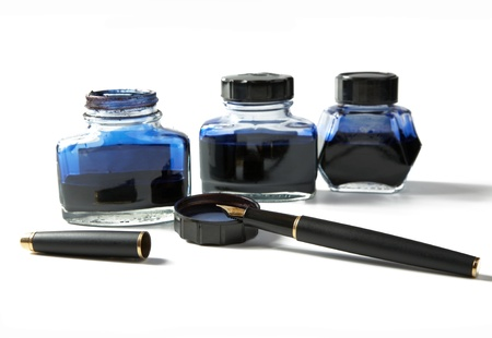 Small bottles with ink and  fountain pen on a white background