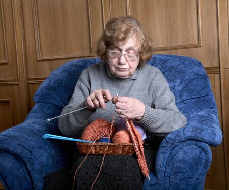 The old woman sits in an armchair and knits Stock Photo