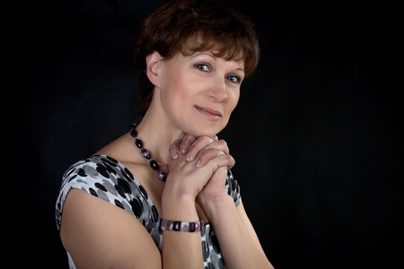 The smiling woman with  beads and  bracelet on  black background