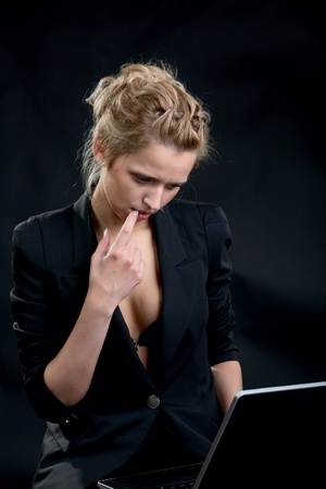 girl in a business suit with the laptop on  black background