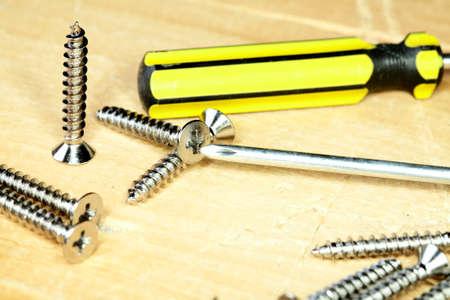 screwdriwer: Screw-driver screws on a wooden board