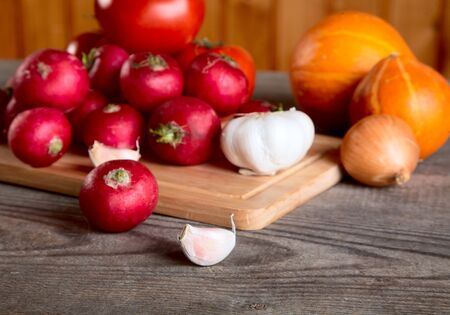 Onions garlic  garden radish on a table from unplaned boards Stock Photo - 9577995