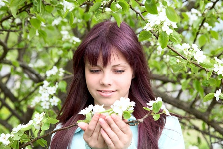 The girl-teenager hold in hand  branch of a pear with flower photo