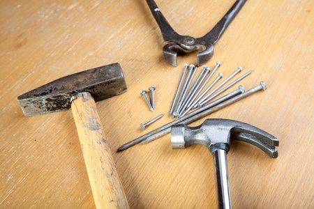 clincher: Hammer nails and pincers on a wooden table