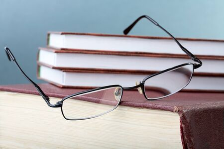 glasses hang down from a pile of books in hard cover Stock Photo - 10102252