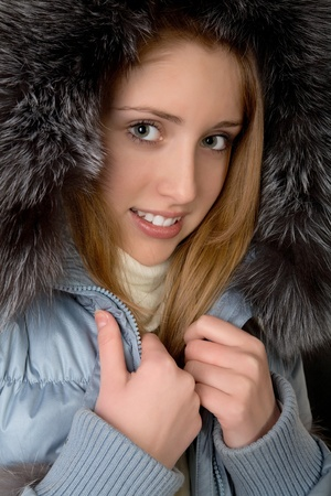 The girl in  warm jacket with a hood on  black background photo
