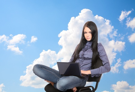girl with the laptop against the sky with clouds photo