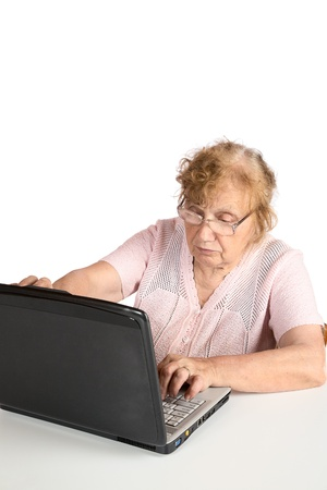 The old woman in glasses looks at the screen notebook on a white background Stock Photo - 10812788
