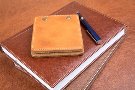 Leather organizers and fountain pen on a textural background