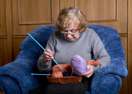 The old woman sits in an armchair and knits photo