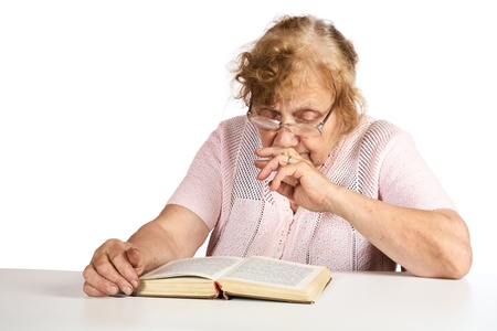 eighty: The old woman in points thoughtfully looks in the book on a white background