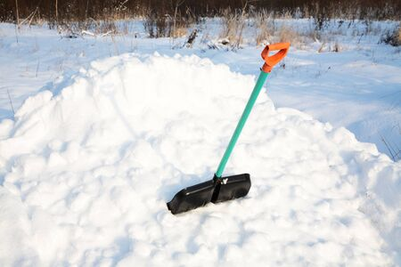 shovel for snow cleaning sticks out in a snowdrift in the winter afternoon Stock Photo - 12015278