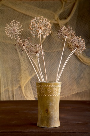 Still-life with dry flowers in a wooden vase photo