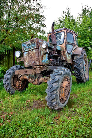 Old tractor against trees (HDRi) photo