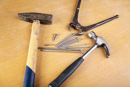 tenailles: Deux marteaux et des tenailles avec des clous sur une table