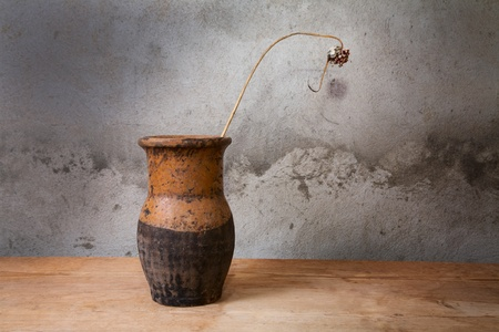 Still-life with an old jug and  dry plant on a wooden table photo