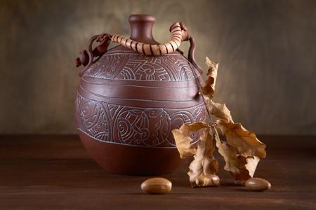 hojas secas: Naturaleza muerta con jarra y seca las hojas de un roble en la mesa