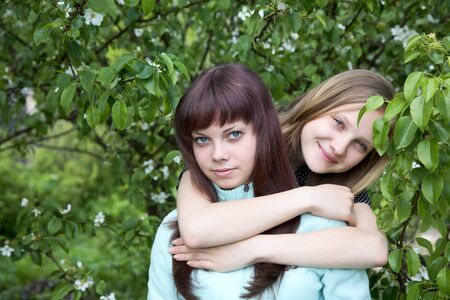 Two girls of the teenager against a blossoming pear in  spring afternoon Stock Photo - 13110691