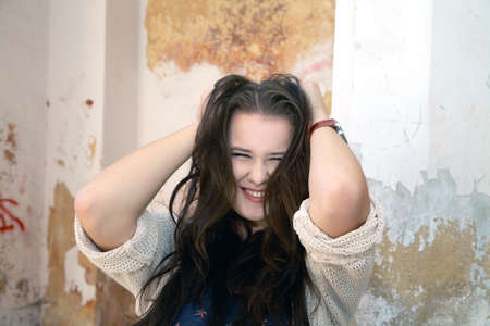 Beautiful plus size woman expresses delight against an old wall photo