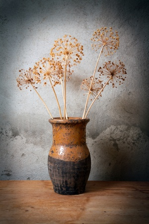 Old jug with dry flower against a cement wall Stock Photo - 13428719