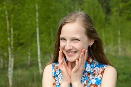 girl with a smile against young birches in the spring photo