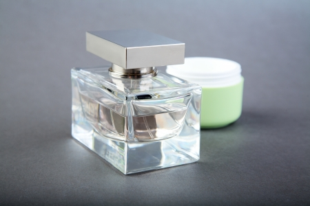 bottle of perfume and  tube of a cosmetic cream on  grey background Stock Photo