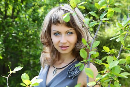 The girl against green foliage in the afternoon Stock Photo - 13901825