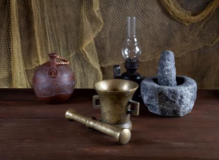 herbolaria: Naturaleza muerta con morteros y una lámpara de aceite sobre una vieja mesa