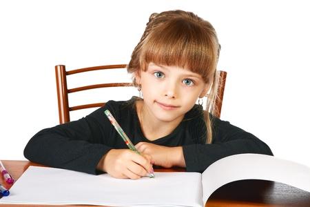 The little girl draws in an album felt-tip pens on a white background