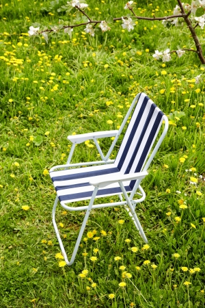 folding chair: Folding chair under a blossoming apple-tree Stock Photo