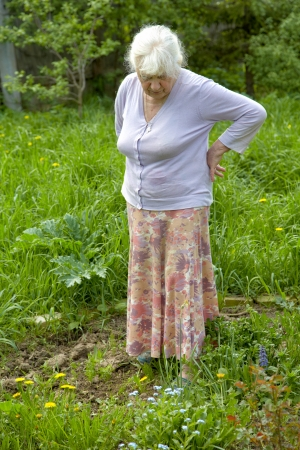 65 70 years: The old woman among a grass in the spring afternoon