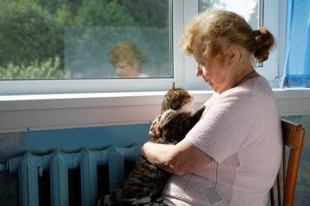 retrato de mujer: La anciana sostiene el gato en una vuelta