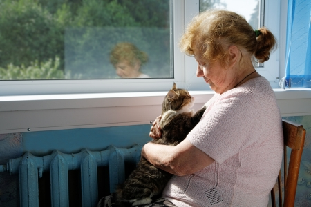 The old woman holds cat in a lap