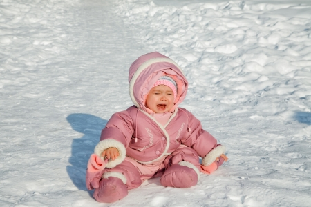 cries: The little girl cries sitting on snow