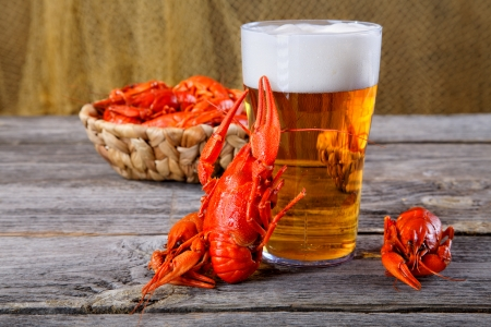 Tasty boiled crayfishes and beer on old table Stock Photo