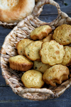 newly baked: Rolls in a wattled basket on an old kitchen table Stock Photo