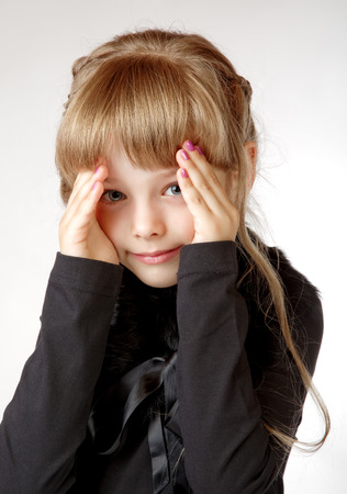 little girl in a black dress shuts  face with the hands
