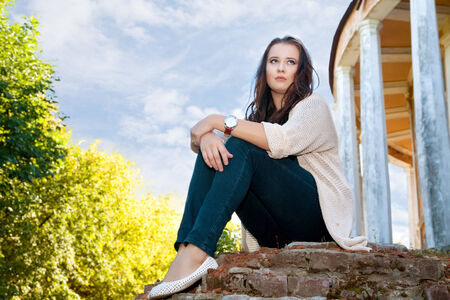 plus size girl sits on an old brick wall in the summer evening