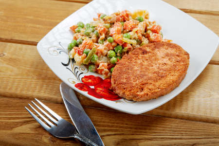 Fish cutlet with a vegetable garnish on a table photo